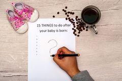 Caption fifteen things to do after your baby is born. White  sheet on a wooden background with a question mark. Caption fifteen things to do after your baby is royalty free stock images