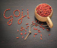 Caption goji berries on a black table, next to a cup filled Royalty Free Stock Photography