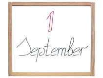 Caption ' 1 September ' is written in red and black marker on a school, white board royalty free stock photography