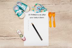 Caption 15 things to do after your baby is born. A4 sheet on a wooden background next to childrens things. Caption 15 things to do after your baby is born. A4 royalty free stock image