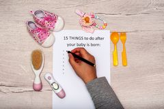 Caption 15 things to do after your baby is born.A4 sheet on a wooden background next to children`s things. Caption 15 things to do after your baby is born. A4 stock photography