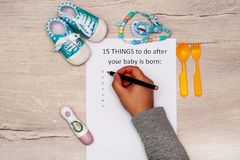 Caption 15 things to do after your baby is born. A4 sheet on a wooden background next to childrens things. Caption 15 things to do after your baby is born. A4 stock photo