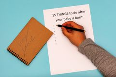 Caption 15 things to do after your baby is born. White A4 sheet on a blue background. Crossed inscription free time. Caption 15 things to do after your baby is stock photo
