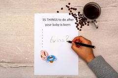 Caption 15 things to do after your baby is born. White A4 sheet on a blue background with the inscription twins. Caption 15 things to do after your baby is born stock image