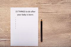 Caption fifteen things to do after your baby is born. White A4 sheet on a wooden background. Caption fifteen things to do after your baby is born. White A4 royalty free stock image