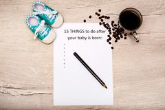Caption 15 things to do after your baby is born. White A4 sheet on a wooden background. Coffee and baby booties. Caption 15 things to do after your baby is born royalty free stock photo