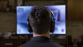 Captivated young man player with big earphones relaxing at home gaming in front of digital monitor TV  -. Captivated young man player with big earphones relaxing stock footage
