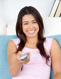 Captivating asian woman holding a remote smiling Stock Photography