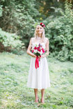 Captivating bride with red wedding bouquet stands in the grass Stock Images