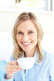 Captivating businesswoman holding a cup on a sofa Stock Photography