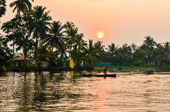 A captivating view of a boat with boatman, trees, houses, landscape on backwaters in Kerala, South india royalty free stock photo