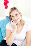 Captivating woman smiling and holding a remote Royalty Free Stock Images