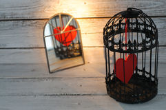 Captive heart in birdcage. Reflected in a mirror Royalty Free Stock Image