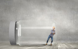 Captive in jar. Builder man trapped in glass jar trying to escape Stock Photos