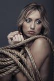 Captivity. Suffering lady bonding by the rope. Studio portrait Stock Image