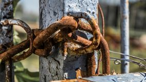 Forgotten and locked in. A captur of an old and rusted chain holding and keep locked an old rusted and destroyed metal door outside in the sun Stock Photos