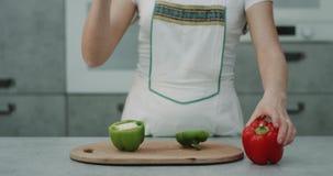 Capturar o vídeo no movimento lento de uma mulher com uma faca grande cortou a cozinha moderna vermelha e verde da pimenta dois d filme