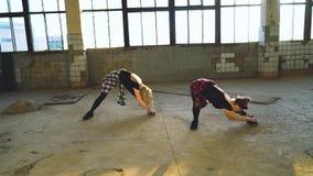 Capture d'écran de deux danseuses qui s'étirent dans le hall d'une ancienne usine avec flare de lentilles banque de vidéos