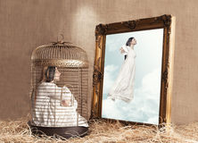 Captured. Young captured woman with white dress in a birdcage looking herself flying freely in a painting