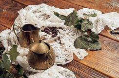 A brass milk jug and a brass sugar bowl with branches of ivy on an old, wooden table top with a white tablecloth and coffee beans royalty free stock photo