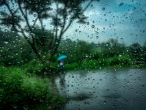 Rain water drops on window glass. Captured in rain from a car. It is car window and blurred person with umbrella in the background Stock Photography