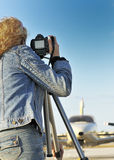 Capturing an Aircraft. Female photographer taking photos at a private airport royalty free stock photography