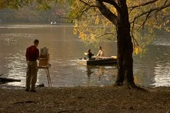 Capturing Autumn Love. Painter capturing the autumn leaves around a lake in central park while couples are enjoying a sunny afternoon rowing around Royalty Free Stock Photography