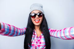 Capturing fun. Happy young African woman in funky clothes making selfie while standing against grey background Royalty Free Stock Images