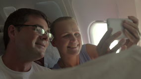 Capturing happy moments together. Slow motion of excited couple making selfie with cell phone in airplane. Taking a shot of happy traveling when they are stock footage