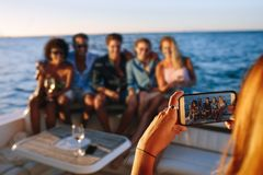 Capturing memories of boat party. Woman taking a picture with mobile phone of her friends sitting on boat. Capturing memories of boat party Royalty Free Stock Images