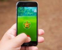 Capturing a Pokemon while playing Pokemon Go Stock Photos