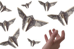 Capturing Profits. A hand trying to catch dollar bills shaped like butterflies. The background is white stock photos