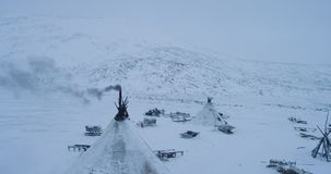 Capturing from the top with drone a camp of yurts in Yamal many sleigh outside the yurts amazing view. Capturing from the top with drone a camp of yurts in stock video