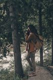 Capturing the view. Full Length of young modern woman with backpack photographing nature while hiking in the woods royalty free stock photo