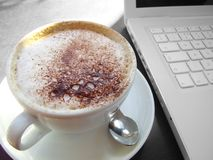 Capuccino. At the Office with a Laptop Background Royalty Free Stock Photo