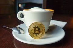 Capuccino and bitcoin gold coin on the table in cafe. Payment by crypto currency concept stock photography