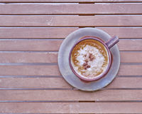 Capuccino coffee in brown cup Stock Image
