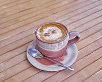 Capuccino coffee in brown cup Royalty Free Stock Photography