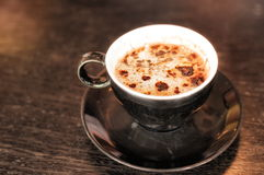 Capuccino coffee. Cup of cappuccino coffee decorated with chocolate on dark table stock photo
