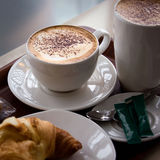 Capuccino and croissant. Breakfast composition with cups of coffee, croissant, sugar etc Stock Photography