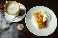 Capuccino, pancake con panna acida e moneta di oro del bitcoin sulla tavola in caffè Fotografia Stock Libera da Diritti