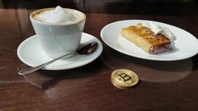 Capuccino, pancake with sour cream and bitcoin gold coin on the table in cafe panorama left to right. stock footage