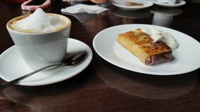 Capuccino and pancake with sour cream on the table in cafe stock video footage