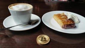 Capuccino, pannekoek met zure room en bitcoin gouden muntstuk op de lijst in koffiepanorama verlaten aan recht stock videobeelden