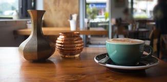 Capuchino caliente en una tabla dentro de una cafetería Foto de archivo libre de regalías