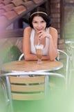 Capuchino de consumición de la chica joven en un café Imagenes de archivo