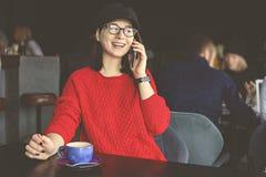 Capuchino de consumición feliz de la mujer joven, latte, macchiato, té, usando la tableta y hablar en el teléfono en una cafeterí imagen de archivo