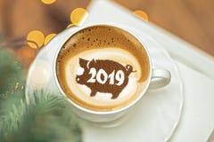 Capuchino del café en una taza con un modelo del símbolo del cerdo 2019 en espuma de la leche Fotos de archivo