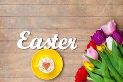 Capuchino y palabra Pascua cerca de las flores Imágenes de archivo libres de regalías