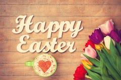 Capuchino y palabras Pascua feliz cerca de las flores Imagen de archivo
